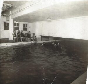 Kaukauna municipal swimming pool located in the basement of the municipal bulding built in the early 1920s.  Photo taken between 1923-1930s.