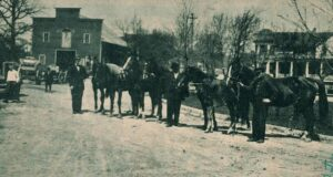 Luther Lindauer and horses. Picture was taken about 1910 in front of what is now the Associated Bank. The livery stable is on the S. W. corner of 4th and Crooks Ave. Across the street is the former Lindauer, Raught, Weckwerh home. At left is Walter Lucht, Unidentified man in middle, probably Luther Lindauer and on right side is Al Maley