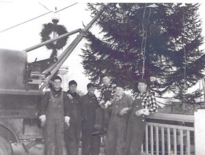 Kaukauna linecrew setting up the municipal Christmas tree. Left to right: Emmett Mc Morrow, Melvin (Smokey) Mainville, Les Wendt, Jack Damro, Fred Vander Bloomen, Bud Heinz. Late 1940s or early 1950s.
