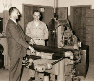 Admiring a milling machine purchased by the Kaukauna Vocational School in 1959 are Dominic Bordini, left, school director and William Roerig, Machine shop and welding instructor.  The machine valued at $8000 was bought for $220 from government surplus.