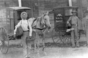Photo shows Levi Pupert, John Kobussen, and Ted Smits standing next to the new mail carriers made by Klumb Wagon Company.